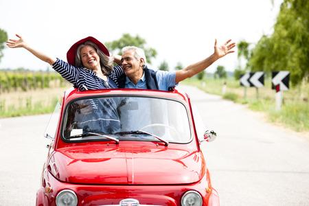 Feliz pareja senior de conducción de coches de época