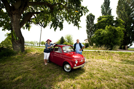 Senior couple with vintage car under a tree photo