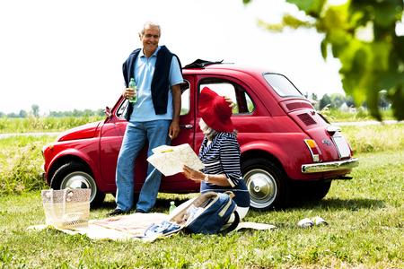 Senior paar met een picknick met vintage auto Stockfoto