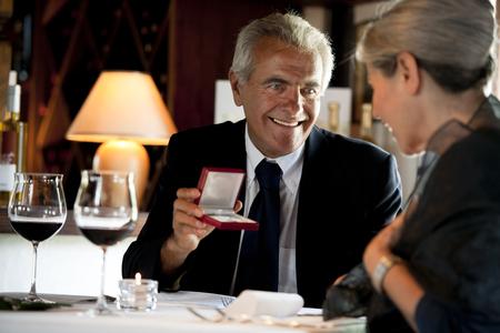 Senior couple at the restaurant, man giving gift photo