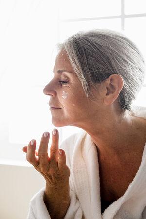 woman face cream: Senior woman applying moisturizer on her face Stock Photo