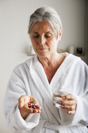 Senior woman holding pills and water in her hands photo