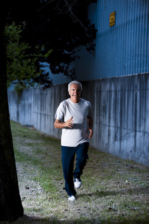 Active senior man running in the evening light photo
