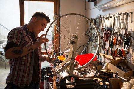 Jonge man aan het werk in een fietsen reparatiewerkplaats