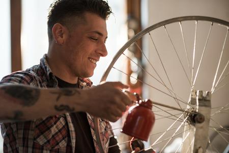 Young man working in a biking repair shop photo