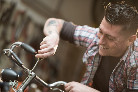 small business owner: Young man working in a biking repair shop Stock Photo