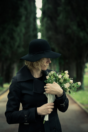 cemetry: Close-up of a sad woman at cemetry holding flowers
