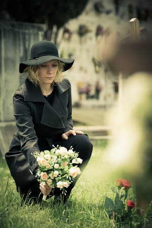 widow: Woman at graveside with flowers
