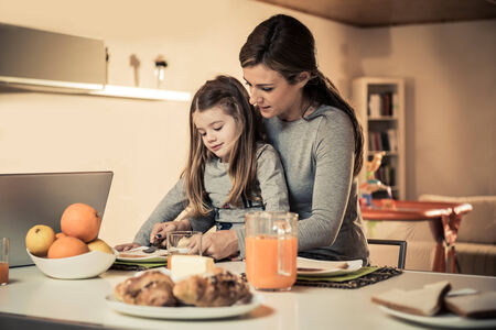 Mother and daughter having breakfast together photo