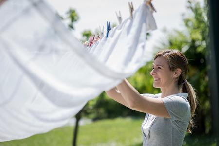ropa colgada: Mujer joven de colgar ropa