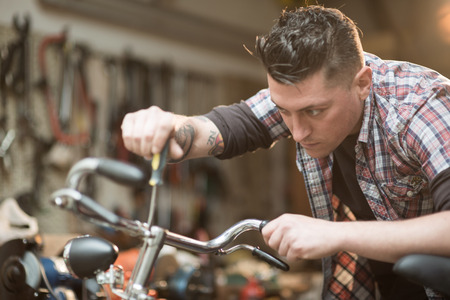 Young man working in a biking repair shop Stock Photo