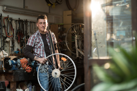 owner: Young man working in a biking repair shop Stock Photo