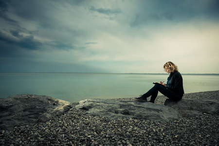 poetry: Woman writing her thoughts or poetry by the sea