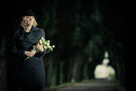 widow: Portrait of a woman at cemetery holding flowers