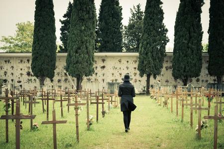 Woman walking in a cemetery Standard-Bild