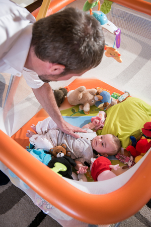 playpen: Father plying with his baby