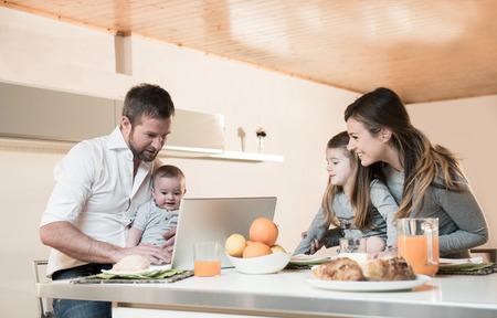 jornada de trabajo: Familia feliz de desayunar, el padre en la computadora portátil con el bebé