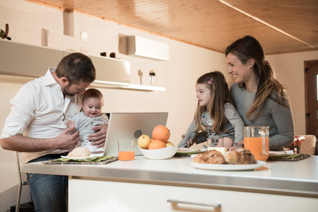 5 6 years: Happy family having breakfast , father on laptop with baby