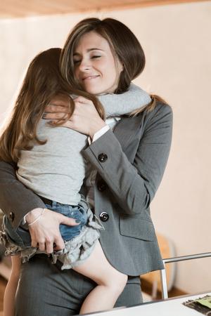 ni�as peque�as: Madre abrazando a su ni�a antes de salir a trabajar  o simplemente de vuelta del trabajo Foto de archivo