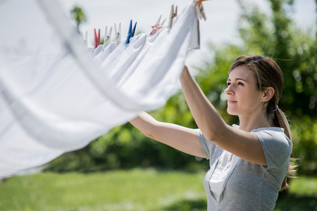 drying: Young woman hanging up laundry
