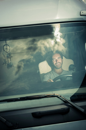 Portret van een vrachtwagenchauffeur zitten in de cabine Stockfoto
