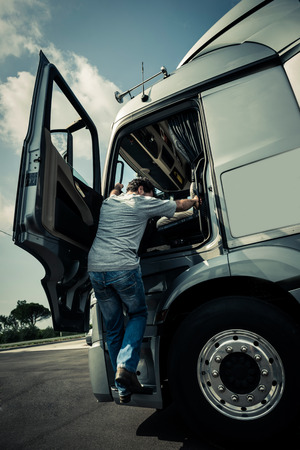 man climbing: Driver climbing into the truck