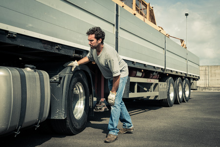 Truck driver working on truck tires Archivio Fotografico