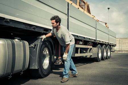 Vrachtwagenchauffeur werken aan vrachtwagenbanden