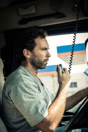 serious: Portrait of a truck driver using CB radio