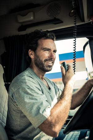 chofer: Retrato de un conductor de cami�n usando radio CB Foto de archivo