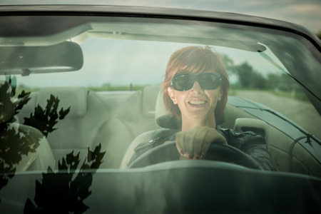 car front: Woman enjoying driving her convertible car Stock Photo