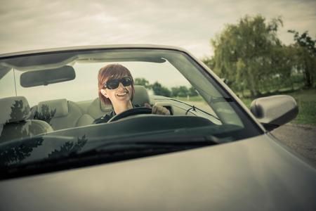 front car: Woman enjoying driving her convertible car Stock Photo