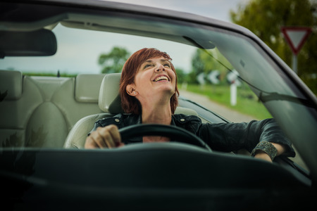 away from it all: Woman enjoying driving her convertible car Stock Photo
