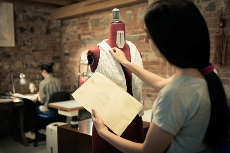 Young fashion designer pinning dress on mannequin Standard-Bild