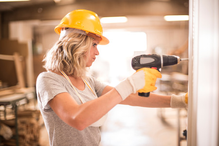 female construction worker: Female carpenter using screwdriver Stock Photo