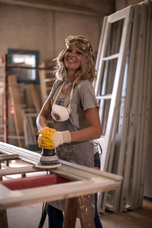 Female carpenter using power sander photo