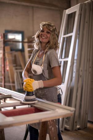 sander: Female carpenter using power sander Stock Photo