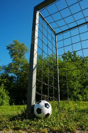 soccer ball is next to the pole of a goal with chains Banque d'images