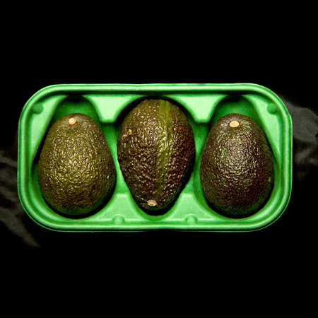 three avocados in a green box