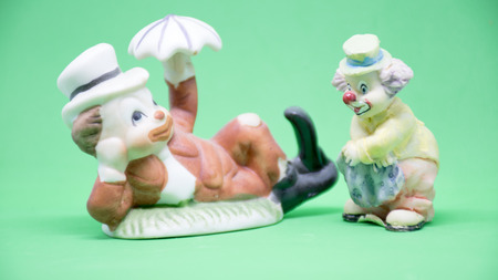 Ceramic puppets on a green background Imagens