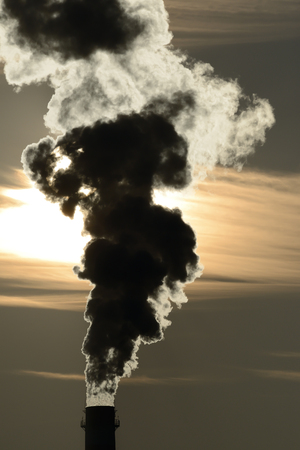 chimney pollutes the air and obscures the sun Stock Photo