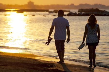 men s feet: A couple Walking On Beach At Sunset Stock Photo
