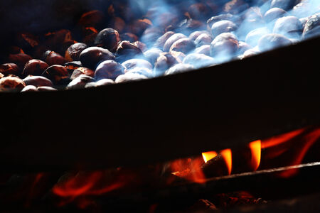 cast iron pan: Roasting Chestnuts in a Cast Iron Pan Stock Photo