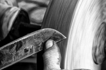 sharpening: Sharpening a knife blade on a wet sandstone grinding wheel