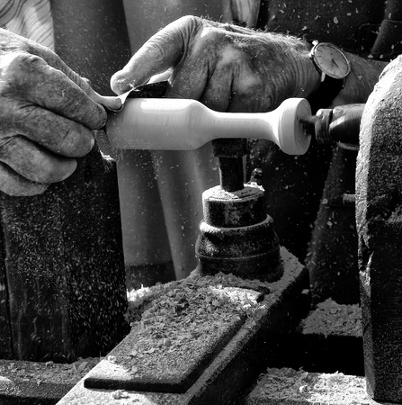 A man using a lathe to carve out a wood product photo