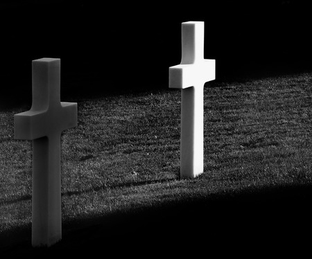 national military cemetery: A ray of sunlight hits a white cross in americans cemetery in Florence
