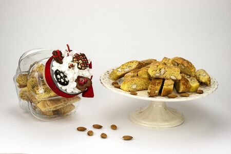 a jar stand: Cantucci, a tipical tuscan biscuits on a white cake stand and jar cookies Stock Photo