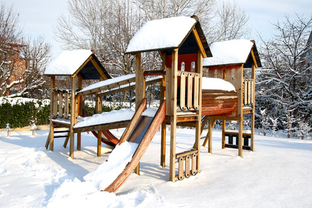 children playground: Children Playground In Public Park Covered With Winter Snow Stock Photo