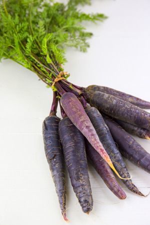 heirloom: Bunch of heirloom purple carrots, over white and wooden background.
