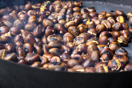 roasting: Organic Brown Chestnuts Roasting over a hot fire .